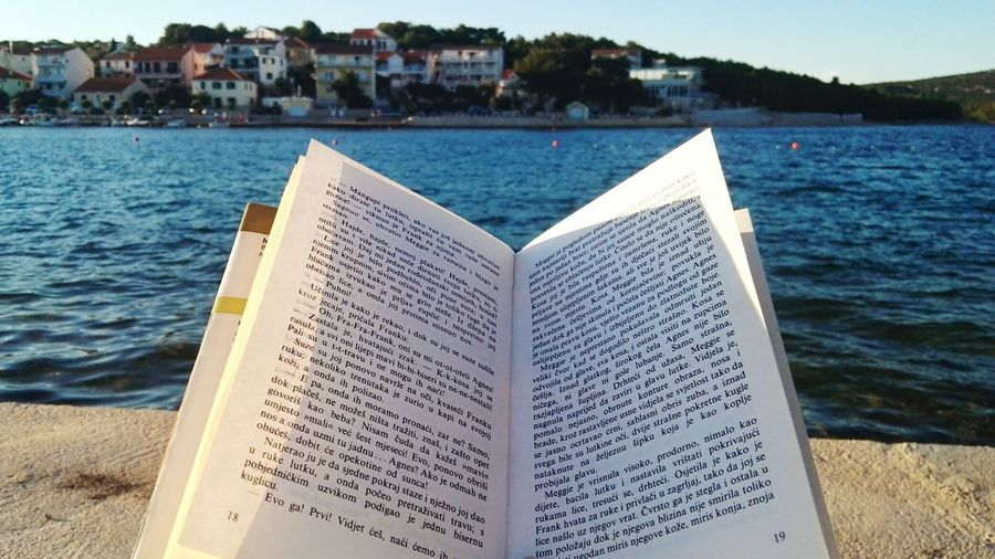 Book by the sea. Book Reading Seaside Island Islandlife Seascape Sea And Sky Sky Blue Colors Colorful Town House Houses City Leasure Activity Activity Paper colour of life EyeEm Selects Water Sea Sky Close-up Shore Calm Wave Coastline Beach Horizon Over Water