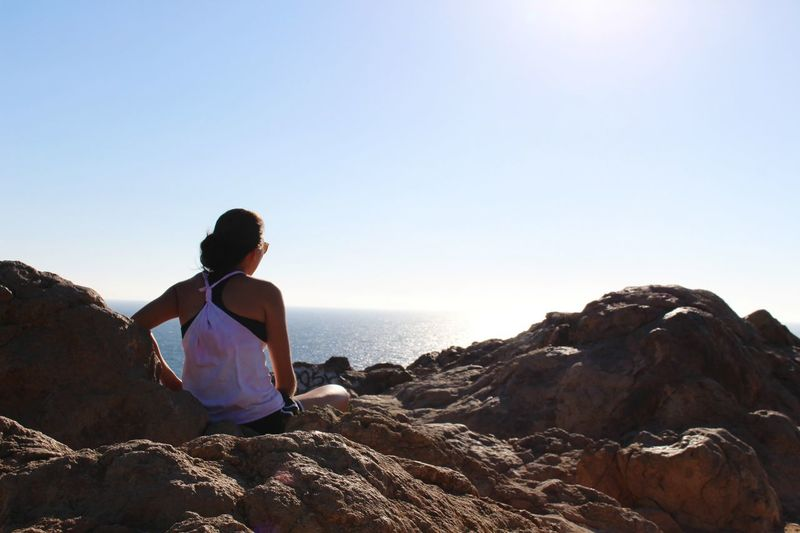 Rear view of woman sitting on rocks by sea against clear sky
