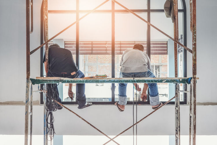Real People People Architecture Rear View Railing Day Window Men Full Length Lifestyles Two People Sitting Built Structure Casual Clothing Nature Outdoors Metal Togetherness Adult Glazier Construction Construction Site Workmanship Skill  Handiwork
