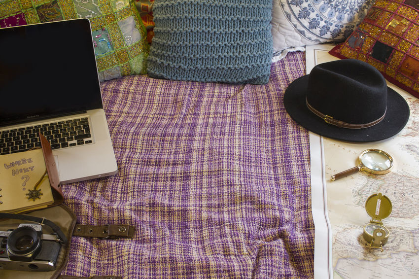 Laptop on comfy bed with blanket and pillows, hat, camera, map and compass Close-up Communication Day High Angle View Indoors  No People Table Technology Wireless Technology