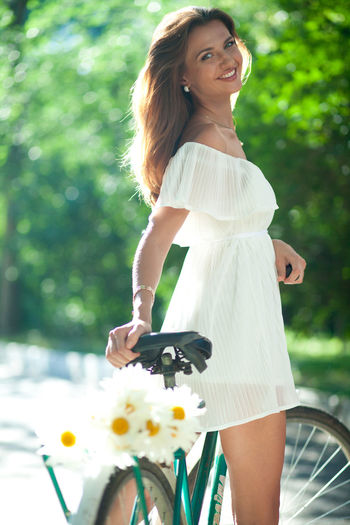 Beautiful young woman in a white summer dress standing and holding on old bike Bicycle Real People One Person Lifestyles Leisure Activity Transportation Women Casual Clothing Young Adult Young Women Smiling Three Quarter Length Day Adult Land Vehicle Hairstyle Mode Of Transportation Beautiful Woman Happiness Riding Hair Outdoors Fashion