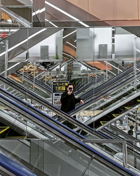 High angle view of man standing on staircase in shopping mall