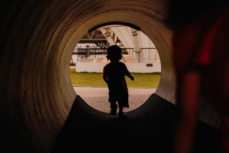 Baby boy walking in concrete tube