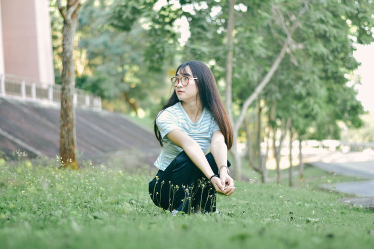 Serious young woman crouching on grass against trees at park