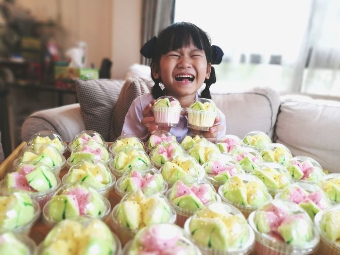 Girl crying while sitting by desserts on sofa at home