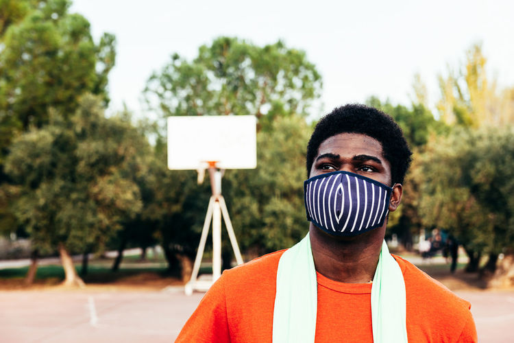 Young man wearing mask at basketball court