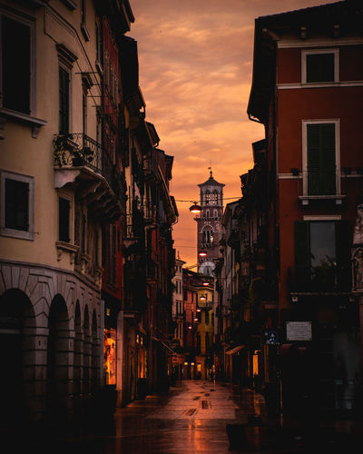 Alley amidst buildings against sky during sunset