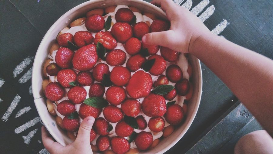 High angle view of hand holding strawberry cake