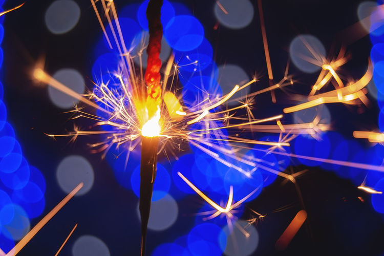 Illuminated Motion Glowing Night Burning Blurred Motion Long Exposure Arts Culture And Entertainment Celebration Sparks Sparkler Close-up Fire Fire - Natural Phenomenon Blue Light Pattern Pieces Circles Bokeh Lights Celebration Firework Heat - Temperature Beauty In Ordinary Things Colored Background