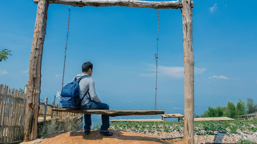 Rear view of backpacker sitting on swing against sky