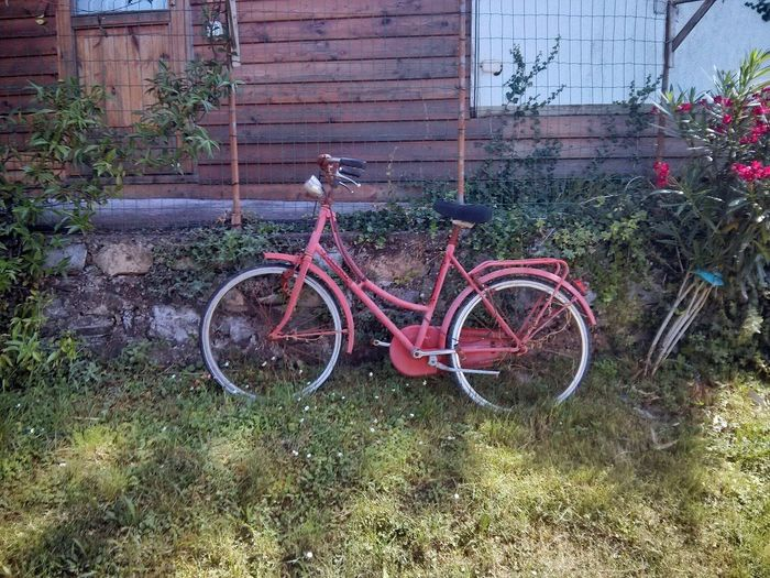 Bicycle parked on field by abandoned building