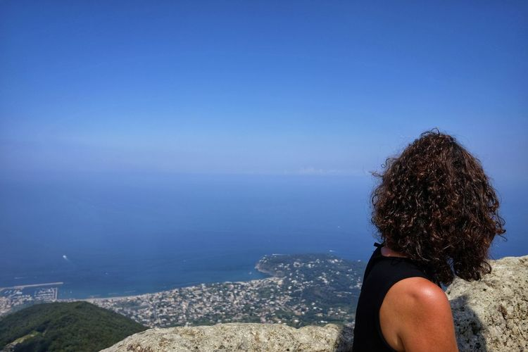 Side view of woman looking at sea against blue sky