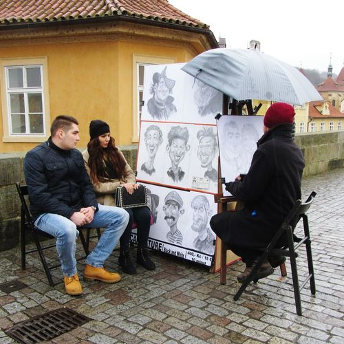 Caricaturist Charles Bridge Prague Artist Street Art People Sitting Umbrella Wintertime Rainy Weather Caricatures Portraits