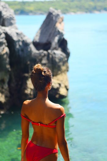 Rear view of young woman standing against sea