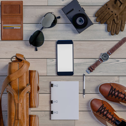 Top view of traveler accessories on wooden. Wood - Material Directly Above Indoors  Table Still Life Large Group Of Objects Shoe Equipment No People Choice Variation Technology Work Tool Connection Tool High Angle View Hand Tool Glasses Flooring Wireless Technology Leather Personal Accessory