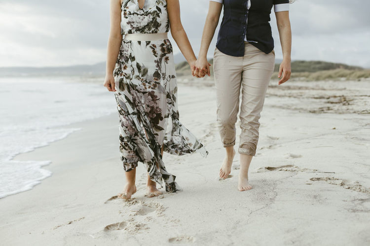 Low Section Of Lesbian Couple Holding Hands While Walking At Beach