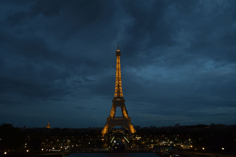 Low angle view of illuminated tower against cloudy sky
