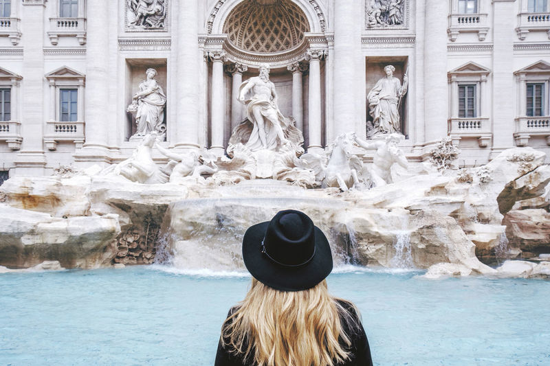 Rear View Of Woman Standing Against Trevi Fountain