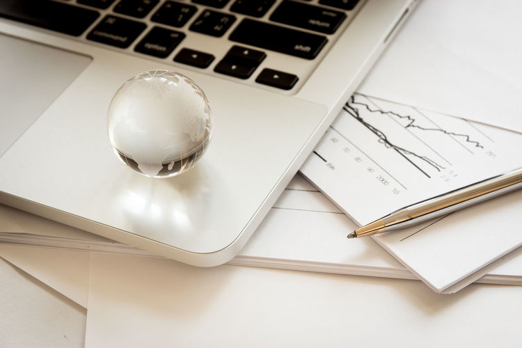 High Angle View Of Globe With Laptop And Files On Table