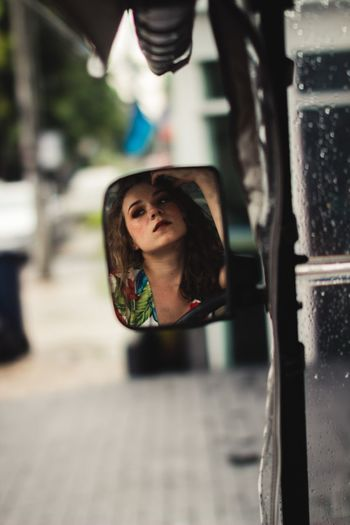 Reflection of woman seen in side-view mirror