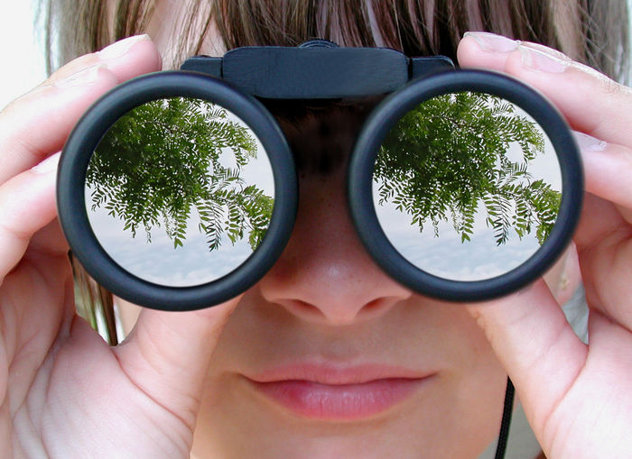 Close-Up Of Woman Looking Through Binoculars