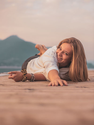 Portrait of young woman lying down against sky
