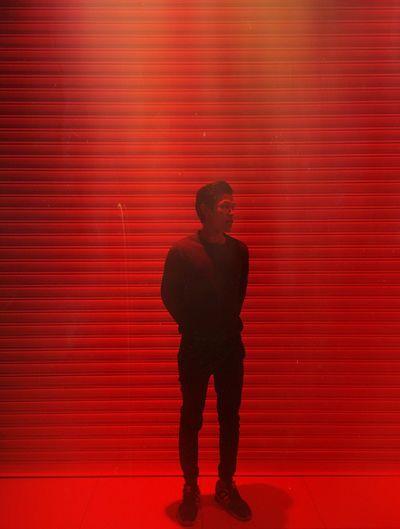 Full length of man standing against red light at night