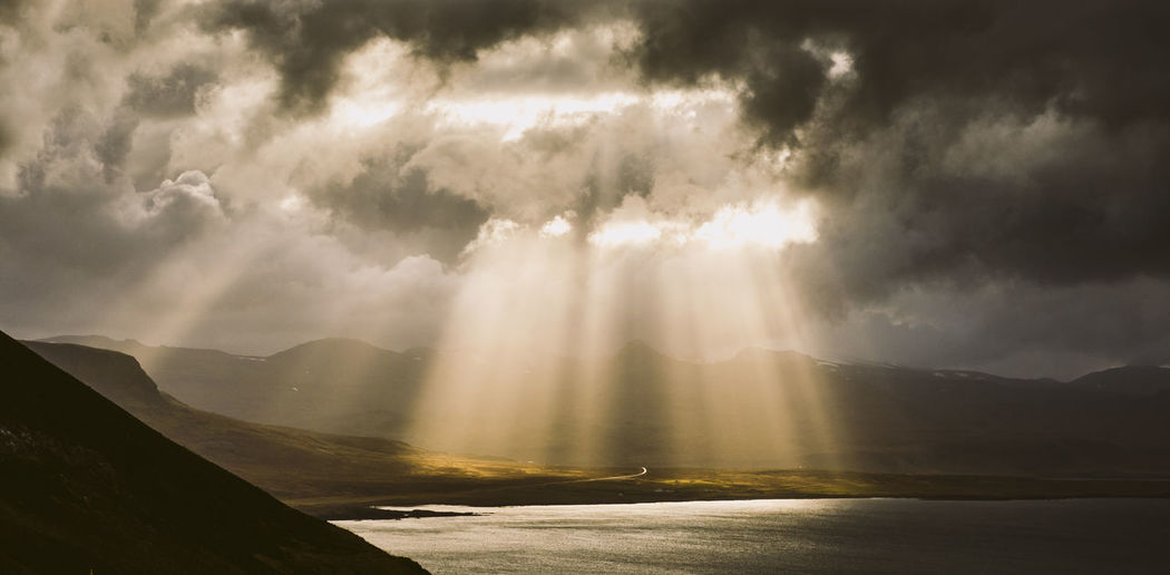 Sunlight streaming through clouds over mountain