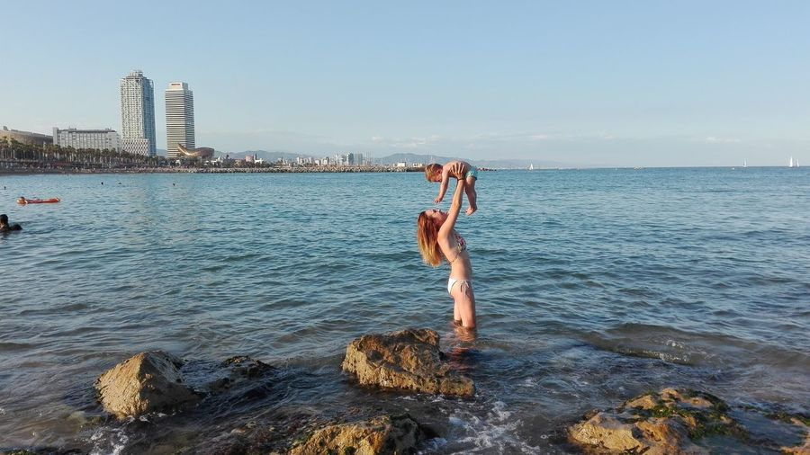 Woman and child in sea by city against sky