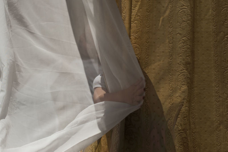 Midsection of woman standing against white curtain