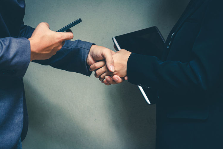Midsection of business people shaking hands with mobile phone and book