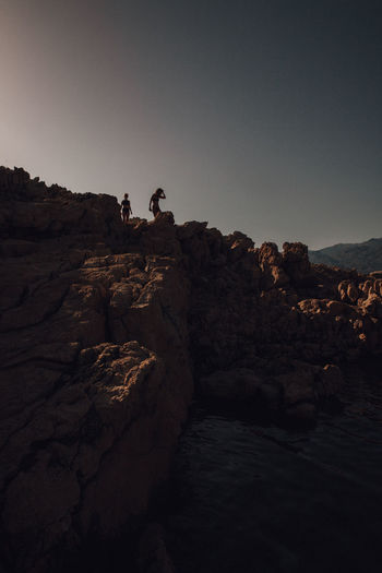 People on rock formation against clear sky