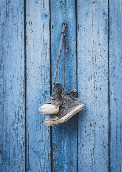 Shoes hanging on old wooden wall