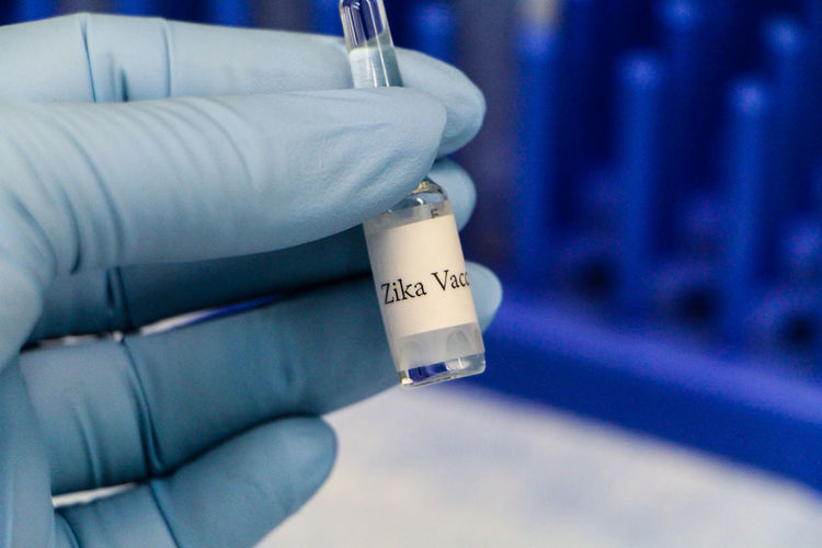 Cropped image of biologist holding zika vaccine at laboratory