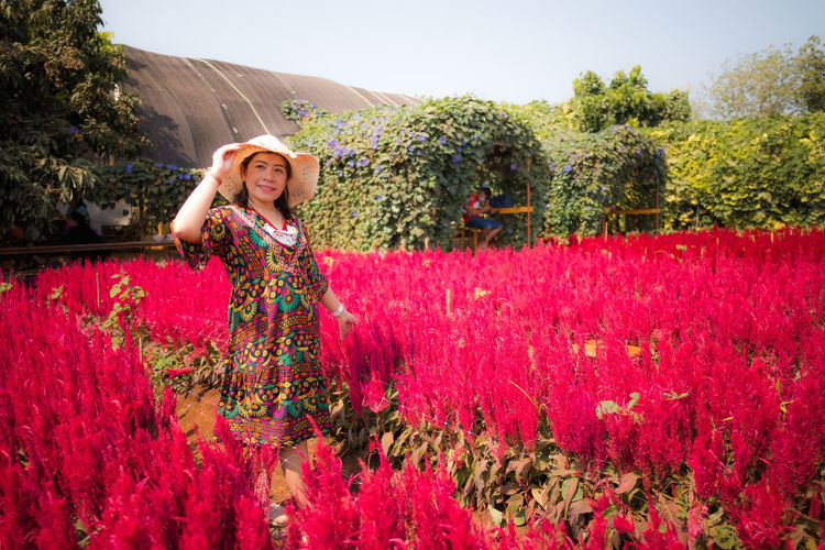 Portrait of woman standing by flowering plants