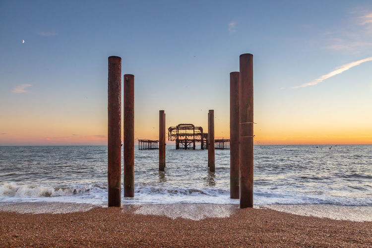 Brightons Iconic West Pier at Sunset, with the Pebble Beach in the Foreground Water Sea Sky Sunset Beach Horizon Horizon Over Water Beauty In Nature Architecture Scenics - Nature Land Nature Built Structure Tranquil Scene Tranquility No People Idyllic Cloud - Sky Architectural Column Outdoors Post West Pier Brighton Iconic Ruins