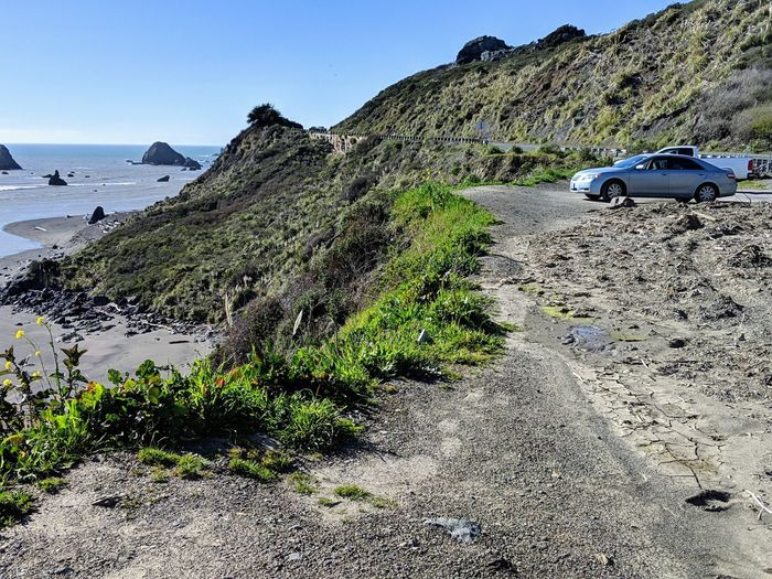 Overlook at ocean. Blue Sky Headlands Dramatic Car Vista Overlook Gravel Dirt Soil View Ocean Sea Waves Zen Diagonal Contrast Background Peaceful Road Country