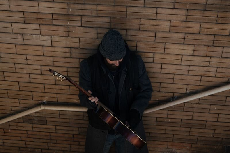 Man Holding Guitar While Standing Against Brick Wall
