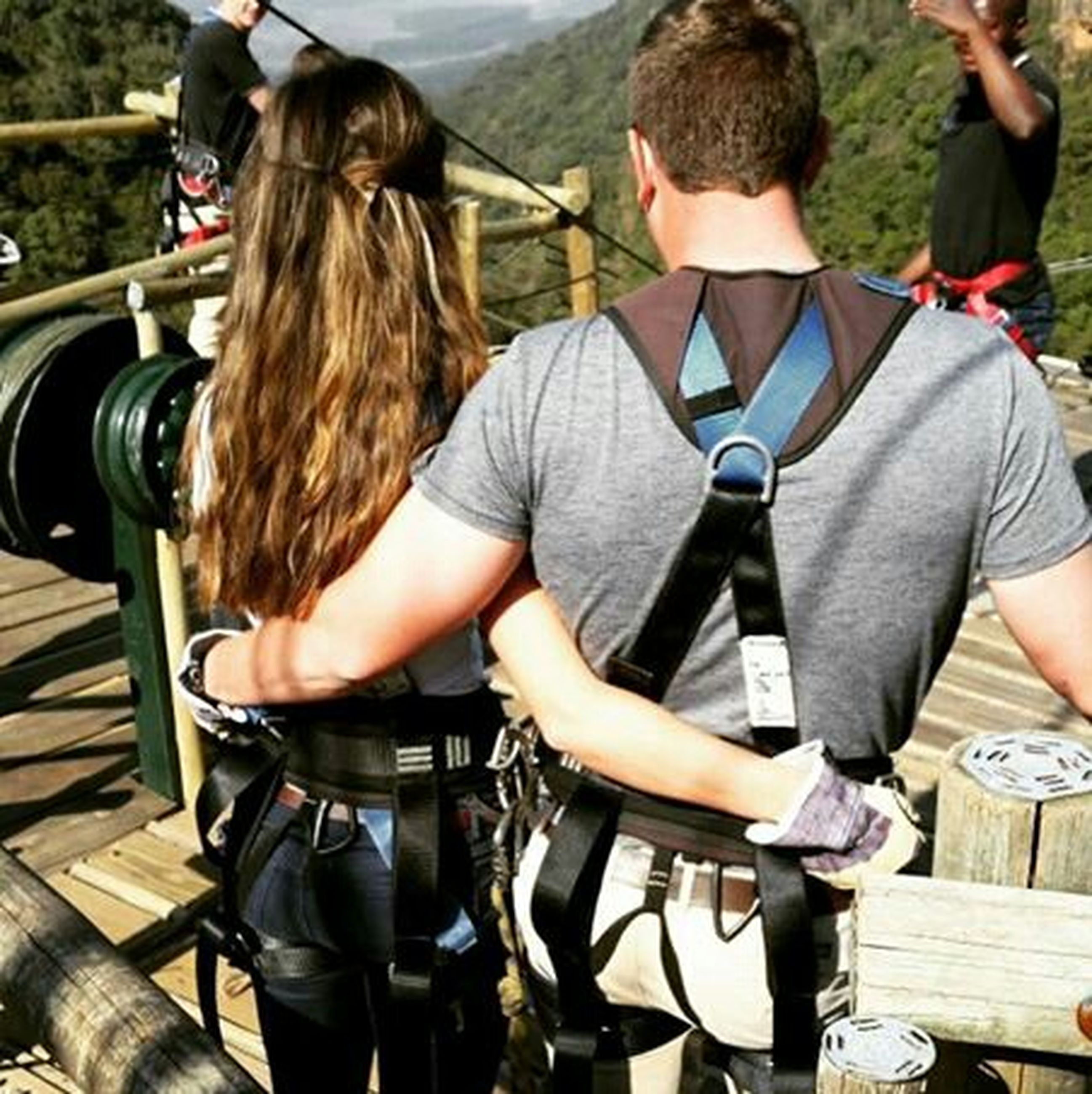 lifestyles, casual clothing, leisure activity, sitting, togetherness, men, standing, person, rear view, friendship, full length, bonding, day, railing, holding