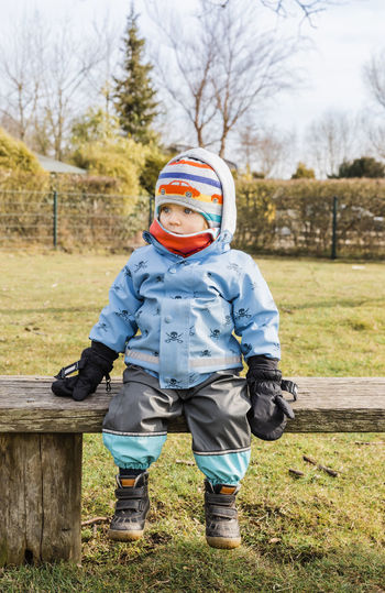 Cute Baby Girl Wearing Warm Clothing While Sitting On Bench During Winter