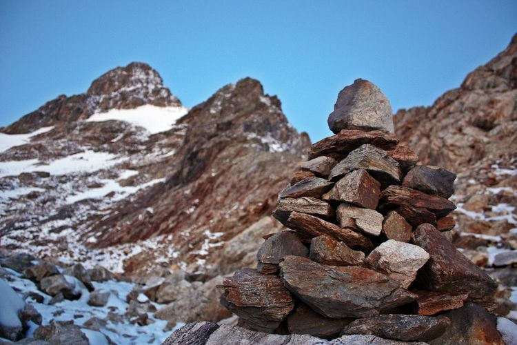 Stacked Rocks Against Mountain During Winter