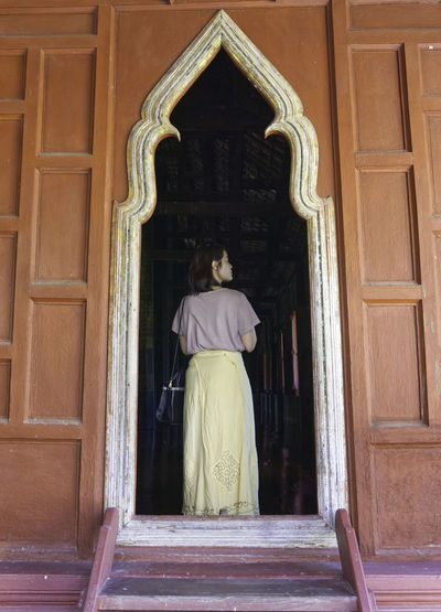Rear view of woman standing at entrance of building