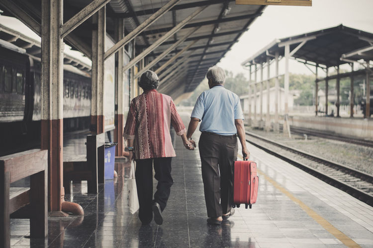Rear view of couple holding hands while walking at railroad station platform