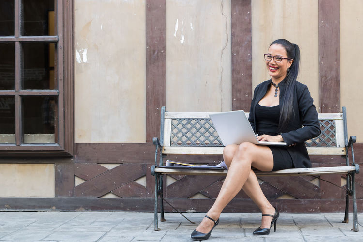 Portrait of businesswoman using laptop on bench