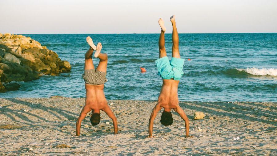 Full length of friends enjoying at beach against sky