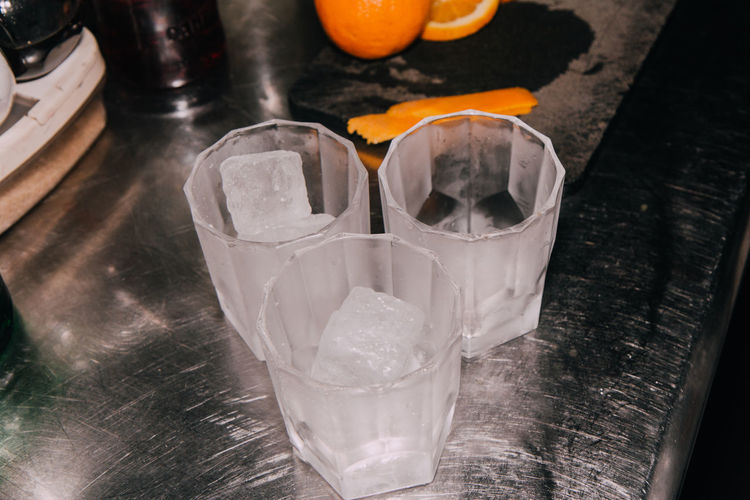 Close-up of ice cubes in drinking glasses on table