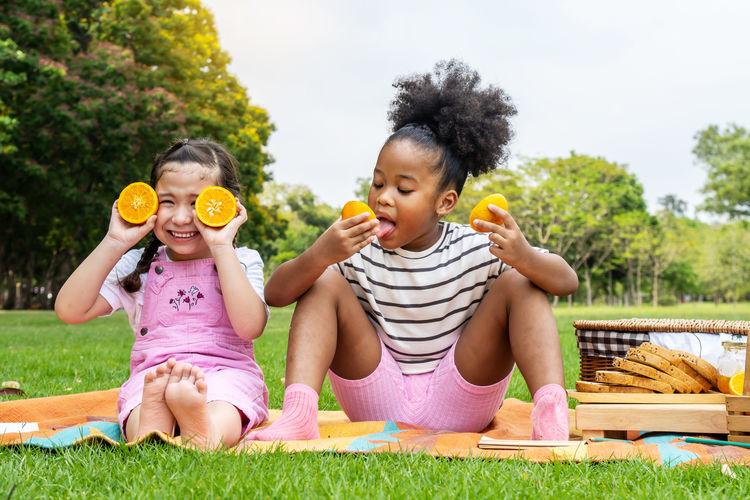 Full length of happy girl sitting on grass