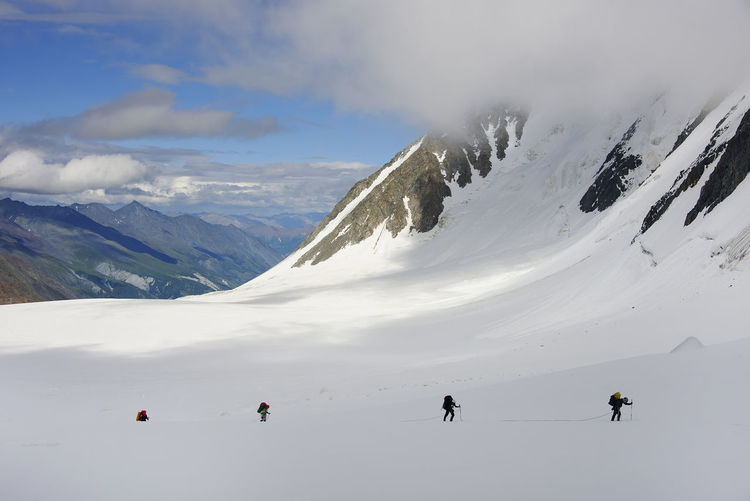 People hiking on snowcapped mountain against sky