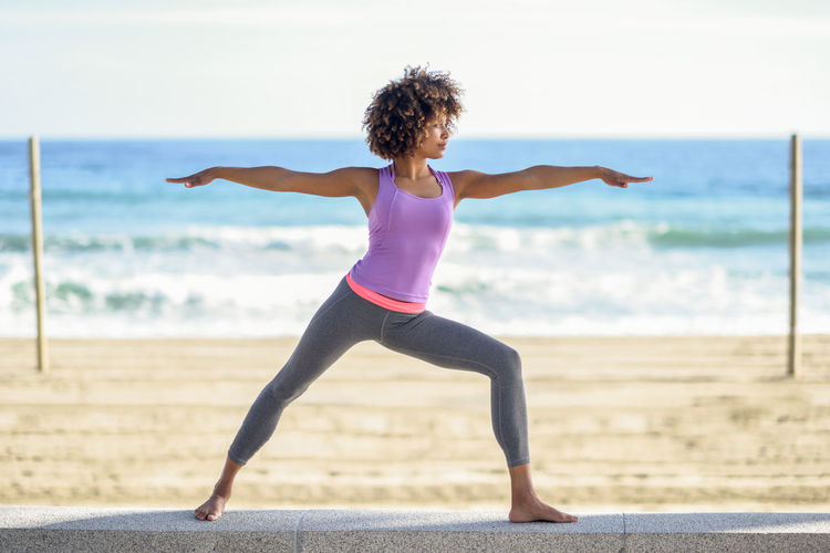Full Length Of Young Woman Performing Yoga Outdoors