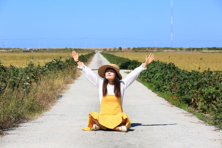 Young woman with arms raised on road amidst field against sky